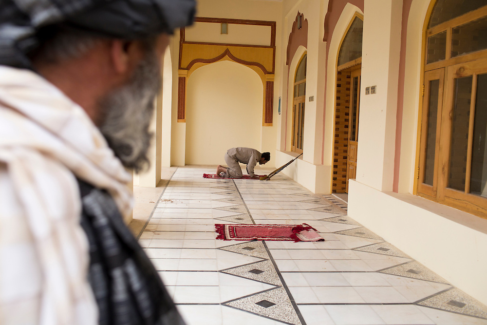 March 23, 2014 - Kandahar, Afghanistan - Hashmat Karzai, cousin of Afghan President Hamid Karzai at his home in their historic village of Karz near Kandahar, Afghanistan. <br /> An armed guard prays at the large mosque within Karzai's fortress-like compound.