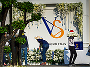 "04 NOVEMBER 2018 - BANGKOK, THAILAND: Workers put the decorations for the funeral of Vichai Srivaddhanaprabha at Wat Debsirin on the second day of funeral rites for Vichai. The VS are his initials. The ""Possible Man"" reflects Vichai's legacy in Leicester because he was viewed as the man who made everything possible after Leicester won the 2015-16 Premier League Championship. Vichai was the owner of King Power, a Thai duty free conglomerate, and the Leicester City Club, a British Premier League football (soccer) team. He died in a helicopter crash at the King Power stadium in Leicester after a match on October 27. Vichai was Thailand's 5th richest man. The funeral is expected to last one week.  PHOTO BY JACK KURTZ"