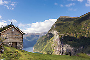 Geirangerfjord is a fjord in the Norwegian county Møre og Romsdal. It is a 15 km long arm of Storfjorden. The village Geiranger is located at the end of the fjord. The picture is captured from Skageflå, an abandoned mountain farm located on a ledge about 250 meters above the fjord, with views to the Seven Sisters waterfalls, and the mountain farm Knivsflå | Geirangerfjorden er en fjord på Sunnmøre i Møre og Romsdal. Den er 15 kilometer lang og utgjør en arm av Storfjorden. Innerst i fjorden ligger Geiranger. Her med utsikt fra Skageflå, en fraflyttet fjellgård som ligger på en fjellhylle ca. 250 meter over fjorden med utsikt til fossene de Syv Søstre og fjellgården Knivsflå.