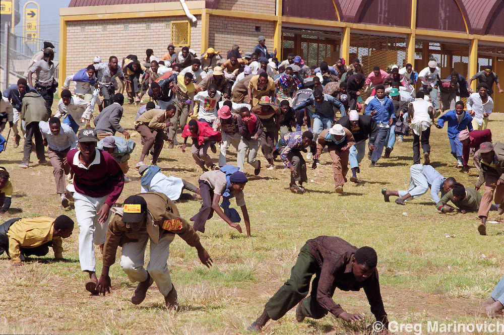 19 April 1993 Soweto, South Africa Hundreds of demonstrators run for cover after police open fire with rubber bullets, tear gas and buckshot outside the Soweto soccer stadium where the funeral of assassinated Communist Party and ANC leadert Chris Hani was held.  Police and rampaging youth clashed after the police were stoned.