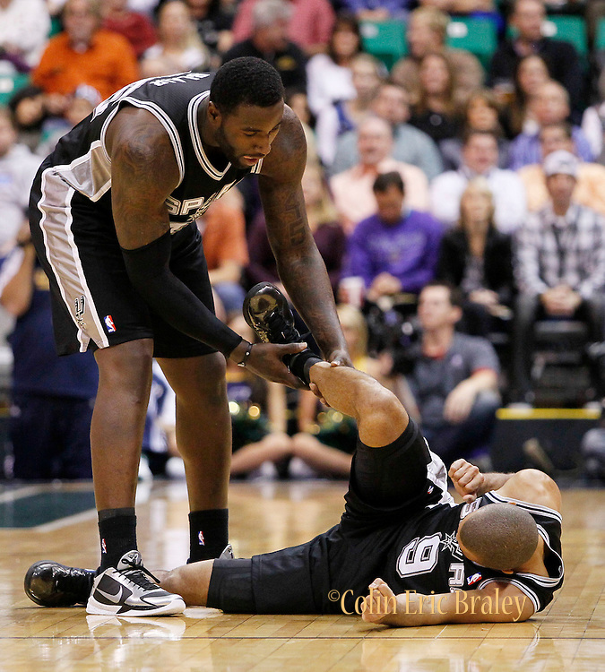 San Antonio Spurs forward DeJuan Blair, left, assists his teammate Tony Parker, right after colliding with Utah Jazz guard Deron Williams during the first half of an NBA basketball game in Salt Lake City, Friday, Nov. 19, 2010. Parker was uninjured on the play. (AP Photo/Colin E Braley)