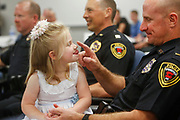Lt. Scott Umbarger taps his daughter Rylee, 4, on the nose as she sticks out her tongue at him during his retirement ceremony from the Springfield Police Department on Friday, April 14, 2017.