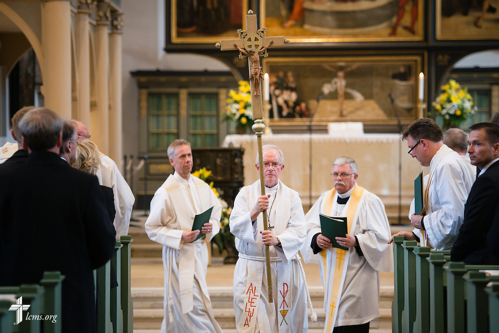 The Rev. David L. Mahsman, LCMS missionary and managing director of the International Lutheran Society of Wittenberg, serves as crucifer in the Festival Dedication Service at the Town and Parish Church of St. Mary's before the dedication of The International Lutheran Center at the Old Latin School on Sunday, May 3, 2015, in Wittenberg, Germany. LCMS Communications/Erik M. Lunsford