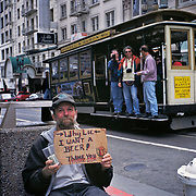 Truthful Panhandler Asks For Beer Money At Union Square; Cable Car In Background With Tourists; San Francisco, CA