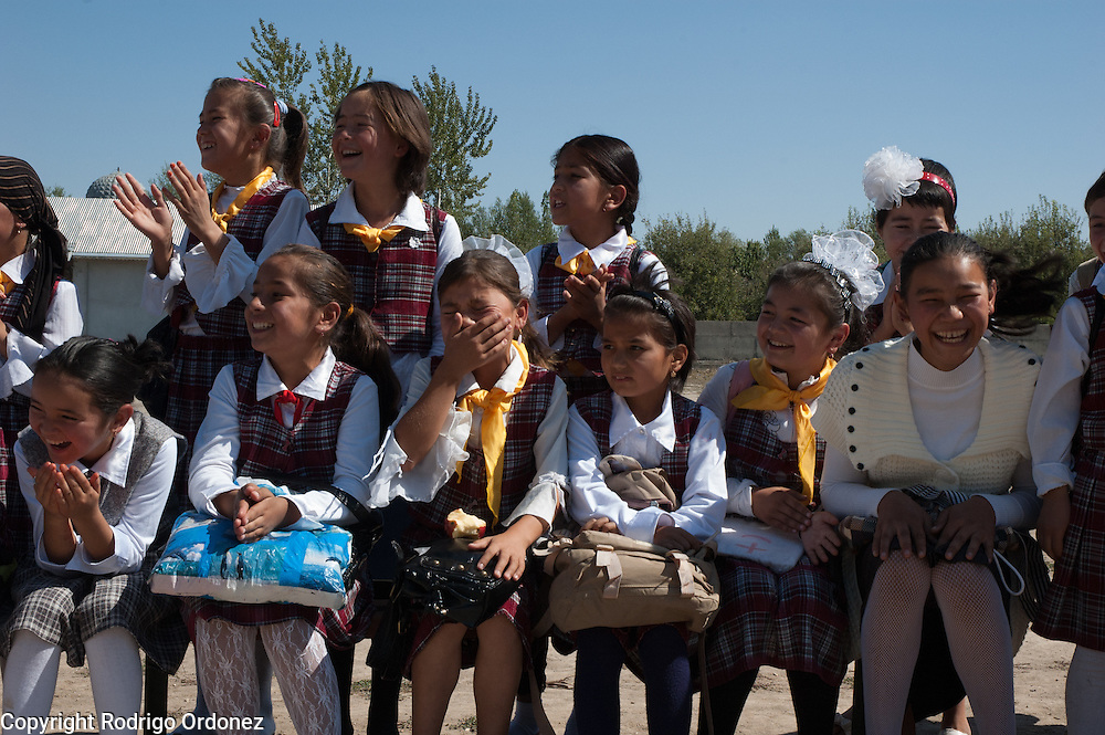 Girls in uniform laugh and cheer their schoolmates during the last day of activities at the child-friendly space located in Alim Tepe School (in Osh, Kyrgyzstan), established and supported by Save the Children. The closing celebrations included a sports competition, games and a cake.