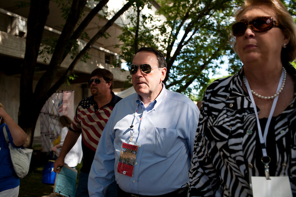 Former Arkansas governor Mike Huckabee, center, and his wife Janet walk around at the Iowa Republican Straw Poll on Saturday, August 13, 2011 in Ames, IA.