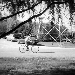 Mrs. Zoerb riding her bicycle on Poplar St. in Heyworth - mid 1970's<br /> <br /> <br /> This image was scanned from a slide, print or transparency.  Image quality may vary.  Dust and other unwanted artifacts may exist.