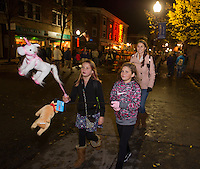 Bella Jenna and Nyla Shosa walk their unicorn and dog down Main Street with Sarah Jenna during Pumpkin Fest Saturday evening.  (Karen Bobotas/for the Laconia Daily Sun)