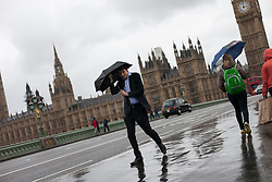 Tourist cover themselves with an umbrella amid rain and wind, at Westminster Bridge, London, UK, 14th May, 2013. Photo by: Daniel Leal-Olivas / i-Images