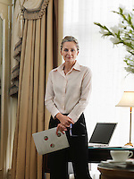 Business woman holding document standing in home office portrait