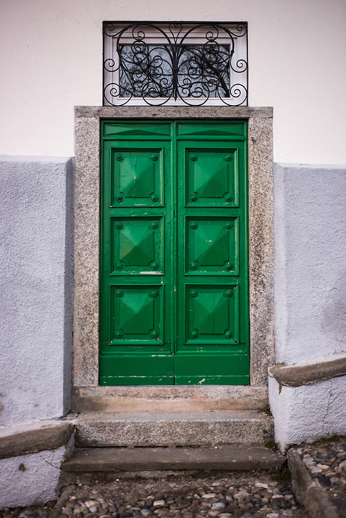 Green decorated door with steps in Santa Maria Del Monte in Varese, Italy illminated at dusk
