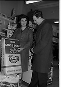 "06/03/1964<br /> 03/06/1964 <br /> 06 March 1964 <br /> New Moss Peat packs introduced by Bord na Mona. Picture shows ""a pretty shop assistant showing the new Moss Peat pack to a customer"" at unnamed store."