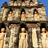 Chedi Kukut Close Up at Wat Chamthewi in Lamphun, Thailand<br /> These are nine of the 60 standing, Dvaravati style Buddha statues inside niches that surround the Chedi Kukut at Wat Chamthewi.  The stupa&rsquo;s square base is 50 feet wide and the five tiers reach a height of 69 feet.  Inside are the ashes of Queen Chama Thewi who became the first ruler of the Haripunchai Kingdom in 663 A.D.