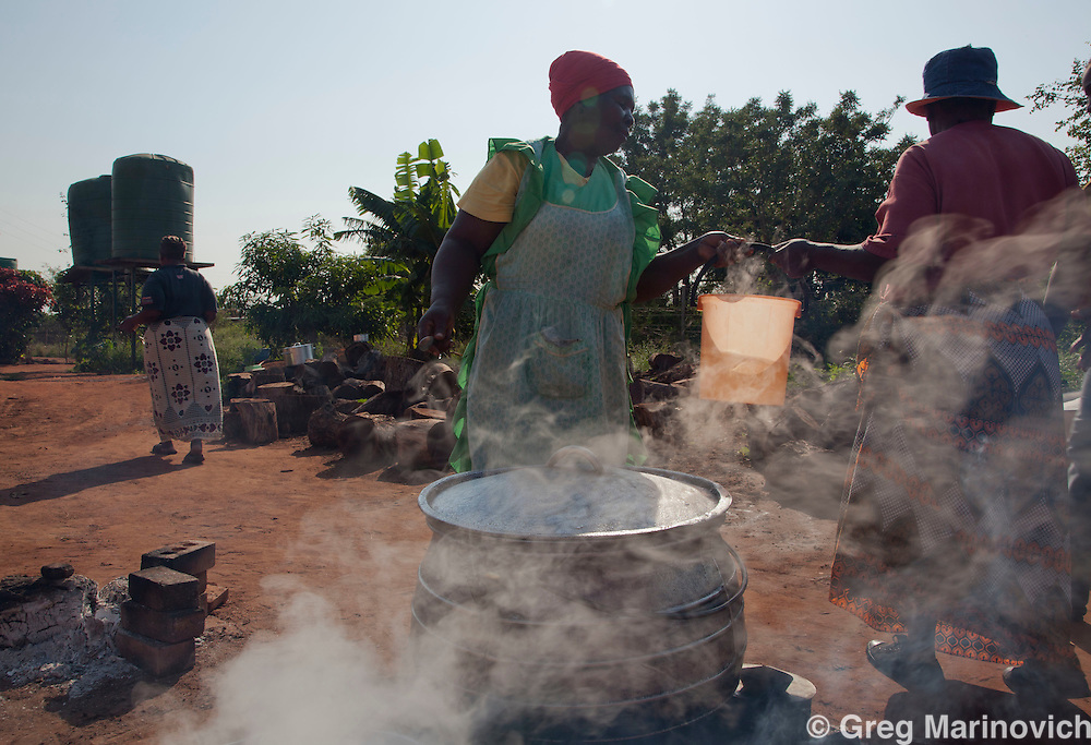 Phakama Trust, Nkomati district, Mpumalanga province, South Africa April 13, 2011: Mothers prepare food with wood fires and water at the Sincobile Secondary School. The combination of urine diversion toilet system and Permaculture garden at Sincobile High School stands out to be the greatest achievement of the Inkomati project. The intention of this pilot project is that the local municipality and the Mpumalanga Provincial Government (and other responsible parties) will be able to duplicate the project in other schools and the community. Photo Greg Marinovich.