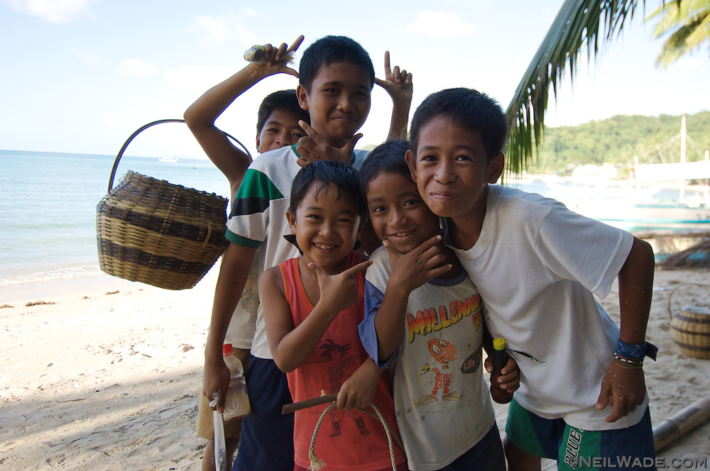 A group of Filipino children smile on the beach in El Nido Town, Palawan, Philippines.