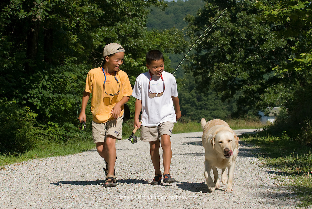 Nine- and seven-year-old brothers, with a yellow Labrador retriever, walk along a road to go fly fishing on the James River, Missouri.