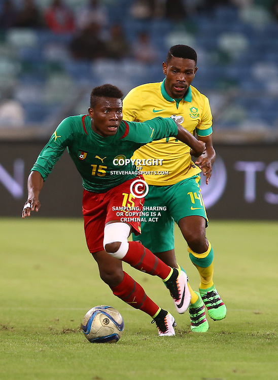DURBAN, SOUTH AFRICA, 29,MARCH, 2016 - Thulani Hlatshwayo of Bafana Bafana looks to tackle Dany Ndi of Cameroon during the match between Bafana Bafana vs Cameroon at Moses Mabhida Stadium in Durban, South Africa. (Photo by Steve Haag)<br /> <br /> images for social media must have consent from Steve Haag