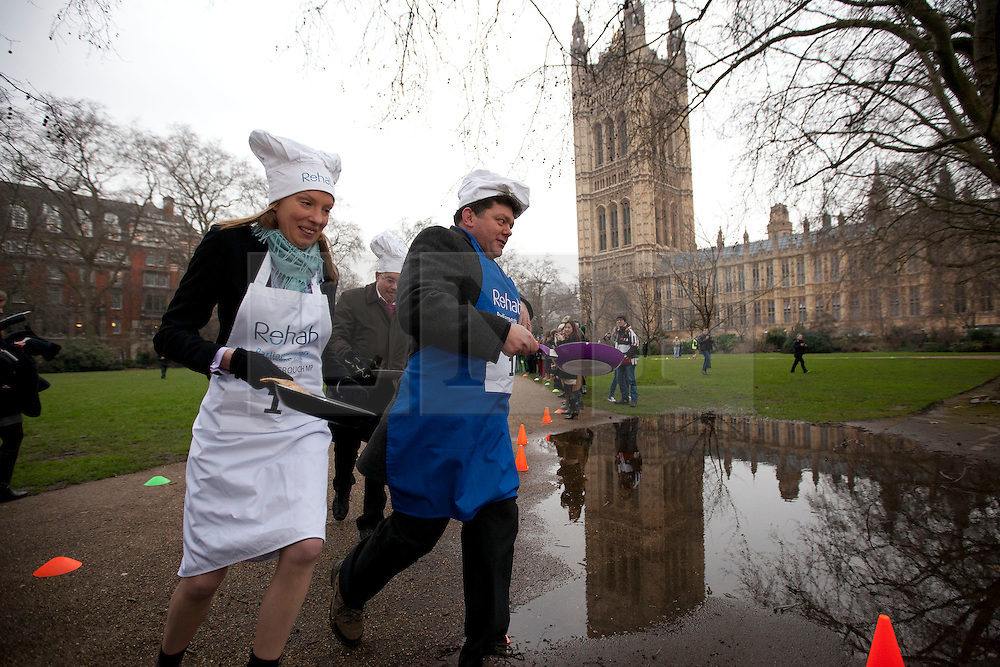 © Licensed to London News Pictures. 12/02/2013. London, UK. British Conservative MP Tracey Crouch (L), Nigel Nelson of the Sunday People (C) and Lord Addington toss pancakes as they take part in the annual Rehab Parliamentary Pancake Race in Westminster, London today (12/02/2013).The race involving MPs from the House of Commons, Lords from the House of Lords and members of the Parliamentary Press Gallery, is aimed at raising awareness for the Rehab; a charity that works to support people with disabilities, takes place every year in Victoria Tower Gardens next to Parliament and was won this year by the House of Commons team. Photo credit: Matt Cetti-Roberts/LNP