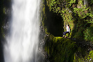 A young woman, sits on a metal safety cable and looks in wonder at beautiful Tunnel Falls on Eagle Creek trail in the Columbia River Gorge, Oregon, USA.  Tunnel Falls received its name due to a tunnel being cut from the bedrock behind the falls so that hikers and trail runners can pass further up the gorge.  The trail becomes very narrow during this section and it is necessary to hold onto a safety cable. (Model Released)