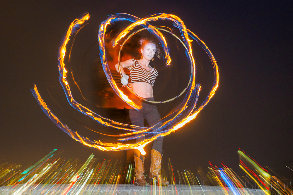 USA, Washington, Seattle. Young woman juggling with fire in an urban park at night. MR