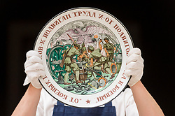 "© Licensed to London News Pictures. 31/05/2019. LONDON, UK. A technician presents ""Feats of Labour"", a Soviet porcelain platter made in the State Porcelain Factory, circa 1921 (Est. GBP 30,000-50,000) at a preview of works from the upcoming sale of Russian Pictures, Works of Art, Fabergé & Icons Sales at Sotheby's, New Bond Street, on 4 June 2019.  Photo credit: Stephen Chung/LNP"