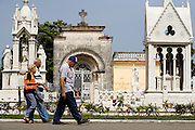 Two elderly men and a woman walk through the Necropolis Cristobal Colon cemetery in Havana, Cuba on Saturday June 28, 2008.