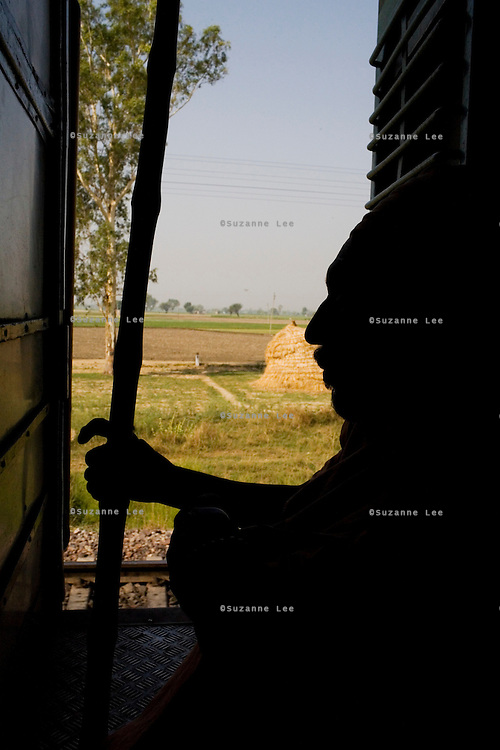 A Punjabi farmer rides for a short while at the door of the Himsagar Express 6318 on 7th July 2009, with the wheat fields of Punjab passing by.. .6318 / Himsagar Express, India's longest single train journey, spanning 3720 kms, going from the mountains (Hima) to the seas (Sagar), from Jammu and Kashmir state of the Indian Himalayas to Kanyakumari, which is the southern most tip of India...Photo by Suzanne Lee / for The National