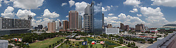 Panoramic view of Houston, Texas skyline featuring Discovery Green in foreground.