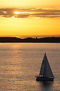 Solitary sailing boat at sea at sunset by the River Solent, UK