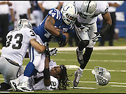 Colts running back Ahmad Bradshaw knocks the helmet off of Raider Mike Jenkins in the second half. The Indianapolis Colts hosted the Oakland Raiders for their home opener at Lucas Oil Stadium on September 8, 2013.