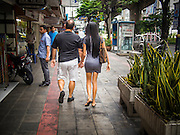 23 JULY 2013 - BANGKOK, THAILAND:  A foreign man and a Thai woman wearing a short skirt hold hands while they walk down Sukhumvit Road in Bangkok.     PHOTO BY JACK KURTZ