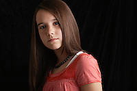 Girl (13-15) on black background portrait