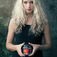 Young woman holding a glass with a red heart inside in her hand and facing the camera