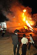 Israel, Haifa, Firefighter extinguish a large bonfire during the lag b'omer celebrations (Lag B'Omer is a day for bonfire celebrations.)