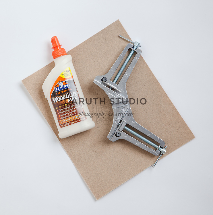 Wood glue, sandpaper, and corner clamp for joining cut base cap molding