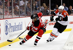 Oct 3, 2009; Newark, NJ, USA; New Jersey Devils defenseman Johnny Oduya (29) skates with the puck past Philadelphia Flyers left wing Mika Pyorala (27) during the third period at the Prudential Center. The Flyers defeated the Devils 5-2.