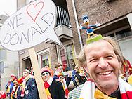 Nederland, Den Bosch, 20170226.<br /> Carnaval in Oeteldonk. <br /> Carnavalsvierder houdt een bord omhoog met de spreektekst: &quot;We love Donald&quot;  <br /> Verwijzend naar de stripfiguur van Donald Duck op zijn hoofd. Veel commotie onder de omstanders dat ieman Donald Trump zou kunnen supporten!! De Donal Duck op zijn hoofd ontgaat hen.<br /> Verklede carnavalvierders vieren feest op straat.<br /> <br /> Netherlands, Den Bosch<br /> Carnival in Oeteldonk.<br /> Partygoer holds up a placard with the text: &quot;We love Donald&quot; in a speech bubble. <br /> Referring to the Donald Duck cartoon character on his head. Much commotion among the bystanders that there could be someone supporting Donald Trump !! The Donal Duck on his head eludes them.<br /> People dressed up in costumes have a party in the streets