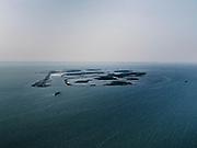 Nederland, Flevoland, Markermeer, 26-08-2019; Marker Wadden in het Markermeer. Overzicht, gezien vanuit het Zuiden, naar kust bij Enkhuizen. Doel van het project van Natuurmonumenten en Rijkswaterstaat is natuurherstel, met name verbetering van de ecologie in het gebied, in het bijzonder de kwaliteit van bodem en water<br /> Naast het hoofdeiland is er inmiddels een tweede eiland in wording, de uiteindelijk Marker Wadden archipel zal uit vijf eilanden bestaan. <br /> Marker Wadden, artifial islands. The aim of the project is to restore the ecology in the area, in particular the quality of soil and water.<br /> The first phase of the construction, the main island, is finished. <br /> <br /> luchtfoto (toeslag op standard tarieven);<br /> aerial photo (additional fee required);<br /> copyright foto/photo Siebe Swart