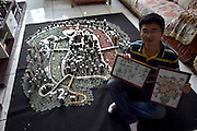 CHONGQING, CHINA - APRIL 29: (CHINA OUT) <br /> <br /> Fifty Thousand Coins To Make Replica Of Chongqing City<br /> <br /> Coin art lover He Peiqi makes up the portrait of Chongqing City with coins on April 29, 2015 in Chongqing, China. He Peiqi, a boy from Yongchuan District of Chongqing put up Chongqing portrait with nearly fifty thousand coins from ancient and the modern within at least 11 currencies of coins in one month. Red agates stand for the Changjiang River, green agates the Jialing River, and every outstanding building makes itself special. The various coins were from He Peiqi\'s small businesses and some were bought from coins lovers. More important that the coins he set up Chongqing City were not stuck together so that he didn\'t break laws of protecting Chinese currencies and thus would not be punished.<br /> ©Exclusivepix Media