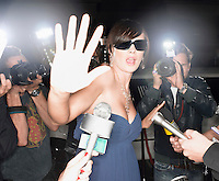 Woman wearing sunglasses escaping from paparazzi