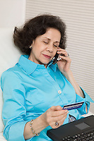 Woman Using Credit Card and Cell Phone to Make Online Purchase