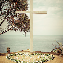 Catalina Island cross picture with heart shaped flowers. The Catalina cross overlooks the city of Avalon California and is used for weddings and other ceremonies. The photo is high resolution and has a vintage retro tone.
