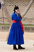 Korean Folk Village. TV movie set. Aristocrat with mobile phone.
