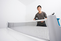 Confident mid adult man playing table tennis