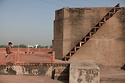 A boy is eating a melon next to a Mughal example of stair in the Ram Bagh Garden in Agra, on the sides of the heavily polluted and semi-dry Yamuna River.