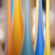 Grouping of several, slender, colorful, hand-blown modern glass bottles. Artist- Ali Shavali
