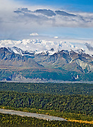 See Denali (20,310 feet or 6191 meters, aka Mount McKinley) from Kesugi Ridge Trail in Denali State Park, Alaska, USA. Denali is the highest mountain peak in North America, and measured from base to peak, it is earth's tallest mountain on land. Mount McKinley is a granitic pluton uplifted by tectonic pressure while erosion has simultaneously stripped away the somewhat softer sedimentary rock above and around it.