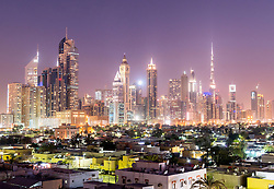 Night view across old Al Satwa district towards modern skyline of Dubai with skyscrapers in United Arab Emirates