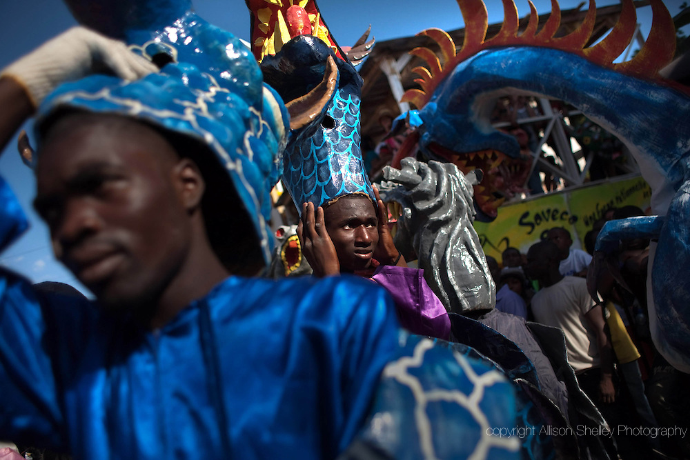 Men take a break from their hot festival masks during carnival weekend in Jacmel, Haiti, February 27, 2011. This year's celebration was met with mixed emotion as the memory of the 2010 earthquake, which forced the cancellation of last year's event, loomed large.