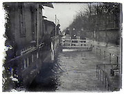people on the bridge of their houseboat during a flood 1900s Paris